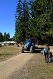 有大绿色树的蓝色农用拖拉机在有蓝天的一条土路 库存照片