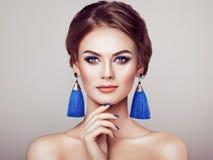 有大耳环缨子的美丽的妇女 免版税库存照片