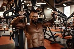 有大肌肉的英俊的人解决在健身房的 做锻炼的肌肉爱好健美者 库存照片