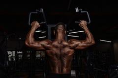 有大肌肉的英俊的人解决在健身房的 做锻炼的肌肉爱好健美者 免版税图库摄影