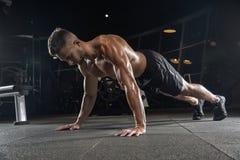 有大肌肉的英俊的人,摆在健身房的照相机 免版税图库摄影
