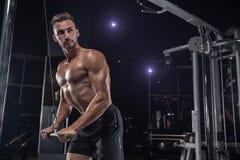 有大肌肉的英俊的人,摆在健身房的照相机 库存照片