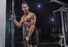 有大肌肉的英俊的人,摆在健身房的照相机 图库摄影