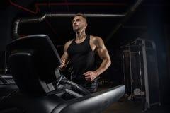 有大肌肉的英俊的人,摆在健身房的照相机 免版税库存照片