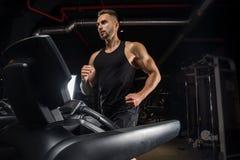 有大肌肉的英俊的人,摆在健身房的照相机 免版税库存图片