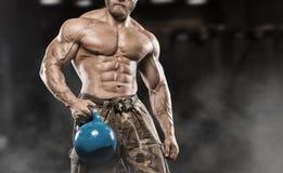 有大肌肉的英俊的人,摆在健身房的照相机 库存图片