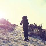 有大背包和雪靴的单独游人走在多雪的道路的使模糊 国家公园阿尔卑斯公园在意大利 老保守冬天天气 库存照片