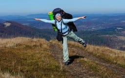 有大背包的女孩游人在喀尔巴阡山脉在秋天 免版税库存照片