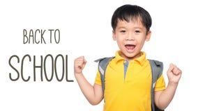 有大背包的快乐的微笑的小男孩跳跃和获得乐趣对白色墙壁 查看照相机 背景黑名册概念copyspace学校 后面t 免版税库存图片