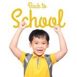 有大背包的快乐的微笑的小男孩跳跃和获得乐趣对白色墙壁 查看照相机 背景黑名册概念copyspace学校 免版税库存照片