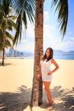 有大胸象的女孩在白色连衣裙由在海滩的棕榈摆在 免版税图库摄影