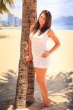 有大胸象的女孩在白色连衣裙由在海滩的棕榈摆在 免版税库存图片