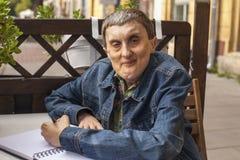 有大脑麻痹文字的年长残疾人在笔记本 免版税库存照片
