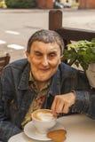 有大脑麻痹的年长残疾人,在一个室外咖啡馆 免版税库存照片