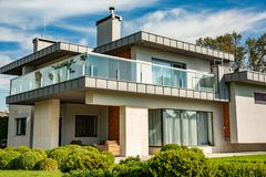 有大草坪和木篱芭的现代乡间别墅 在房子前面有与休息室区域的一个被盖的大阳台 免版税库存照片