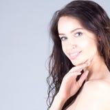 有大蓝眼睛和卷发的愉快的美丽的少妇微笑与牙的 美丽的表面妇女 免版税库存照片
