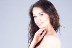 有大蓝眼睛和卷发的愉快的美丽的少妇微笑与牙的 美丽的表面妇女 免版税图库摄影
