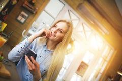 有大蓝眼睛的妇女与电话在手中作梦关于某事的在新年假日装饰的咖啡馆 免版税库存照片