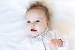 有大蓝眼睛的美丽的女婴在白色bl 免版税库存图片