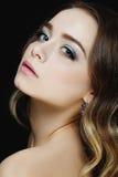 有大蓝眼睛的美丽的白肤金发的女孩在黑背景 库存图片
