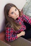 有大蓝眼睛的美丽的迷人的年轻可爱的女孩与黑暗的长的头发在秋天天坐台阶 库存照片