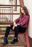 有大蓝眼睛的美丽的迷人的年轻可爱的女孩与黑暗的长的头发在秋天天坐台阶 免版税库存照片