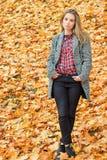 有大蓝眼睛的美丽的迷人的年轻可爱的女孩,与长的黑发在外套的秋天森林里 库存照片