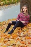 有大蓝眼睛的美丽的迷人的年轻可爱的女孩,与长的黑发在秋天森林坐叶子在Th附近 免版税库存图片