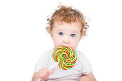有大蓝眼睛的逗人喜爱的婴孩用一个五颜六色的糖果,被隔绝 图库摄影