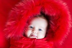 有大蓝眼睛的逗人喜爱的滑稽的女婴在温暖的夹克 免版税库存照片