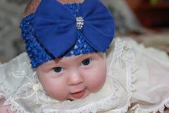 有大蓝色弓的新出生的女孩 免版税库存图片