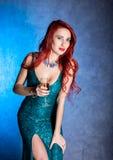 有大蠢材的典雅的性感的妇女在拿着葡萄酒杯用香槟的紧的蓝色礼服 免版税库存照片