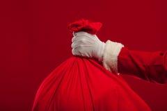有大袋子的圣诞老人在肩膀玻璃红色背景 免版税库存图片