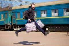 有大袋子的年轻人跑在火车站 免版税库存照片