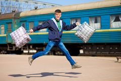 有大袋子的年轻男孩跑在火车站 免版税库存图片