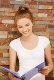 有大记事本的愉快和微笑的十几岁的女孩 库存图片