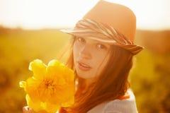 有大郁金香花日落ligh的年轻可爱的浪漫女孩 免版税库存图片
