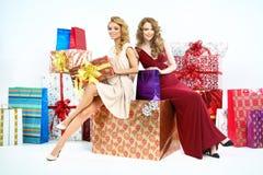 有大量的两名可爱的妇女圣诞节礼物 图库摄影