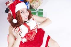 有大量的微笑的性感的白种人姜圣诞老人帮手女孩五颜六色的当前箱子 库存照片