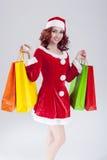 有大量的性感的白种人姜圣诞老人帮手女孩五颜六色的购物袋 免版税库存照片
