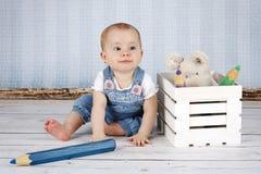 有大铅笔和长毛绒玩具的笑的小女婴 库存图片