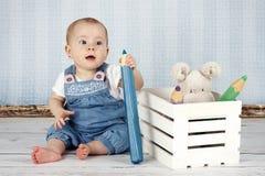 有大铅笔和长毛绒玩具的笑的小女婴 免版税库存图片
