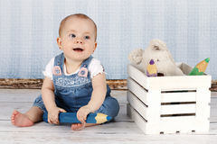 有大铅笔和长毛绒玩具的笑的小女婴 图库摄影