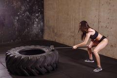 有大锤的妇女非凡的大轮胎在适合健身房的强烈的锻炼期间 免版税库存图片