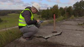 有大锤的工作者使用在残破的混凝土板附近的片剂个人计算机 股票录像