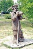 有大镰刀的喝从水罐的一位农夫的雕象 库存照片