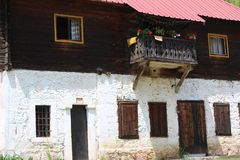 有大阳台的老在willage Stitkovo的房子和花在塞尔维亚 免版税库存照片