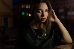 有大嘴唇的美丽的性感的女孩有在一条城市街道上的红色唇膏的在灯笼附近的晚上 库存图片