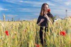 有大嘴唇的美丽的性感的逗人喜爱的女孩和在一件黑夹克的红色唇膏有站立在鸦片的花鸦片的调遣在日落 库存图片