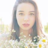 有大嘴唇的美丽的性感的逗人喜爱的女孩和有露出的肩膀的红色唇膏与雏菊花束在日落的在晴朗温暖 免版税库存照片